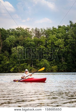 Woman is kayaking on a small lake in Central Kentucky