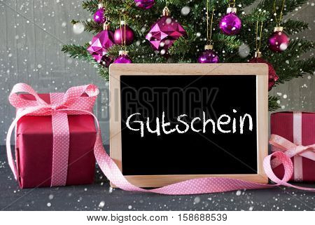 Chalkboard With German Text Gutschein Means Voucher. Christmas Tree With Rose Quartz Balls, Snowflakes. Gifts Or Presents In The Front Of Cement Background.
