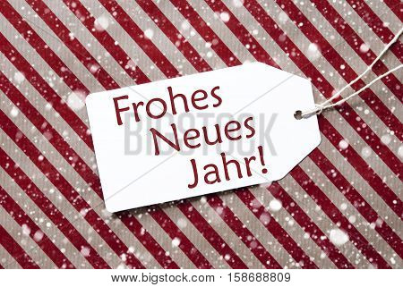 One Label On A Red And Brown Striped Wrapping Paper. Textured Background With Snowflakes. Tag With Ribbon. German Text Frohes Neues Jahr Means Happy New Year