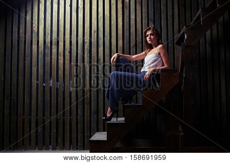 An irresistible deep regard of modern trendy young woman on high heel shoes sitting on stairs in studio