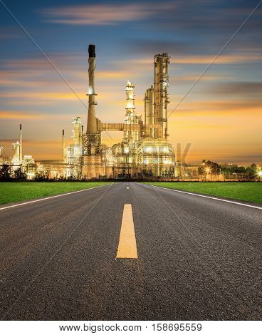 Oil refinery factory and asphalt road at twilight with sky background.