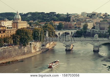 Ponte Vittorio Emanuele II and River Tiber with tourism boat in Rome, Italy.