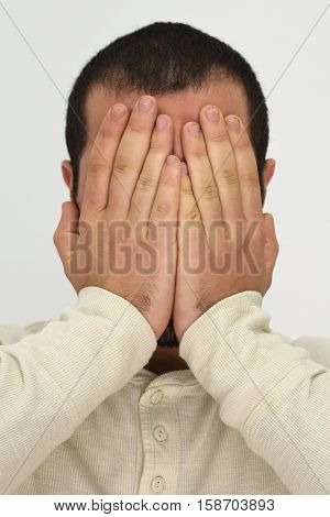 A picture showing a man covering his face with his palms
