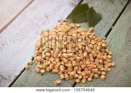 Wood pellets on a blue wooden background, two green leaf from a tree.Biofuels. Cat litter.