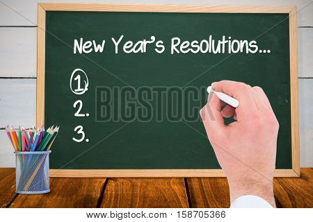 Hand of businessman writing with a white chalk against composite image of black board Composite image of black board against wooden planks