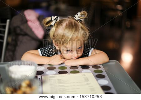 Elementary age girl sitting at the table in cafe. Girl waiting for her order. Girl is bored sitting at the table. Facial closeup portrait of a little girl in a cafe. Girl sink head on arms.