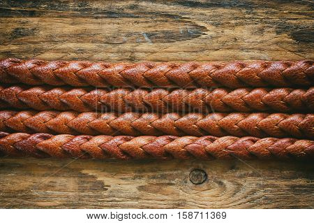 detail texture natural brown leather belt braided pigtail on wooden old table