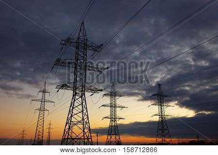 Metal Bearing high voltage power line at sunset.