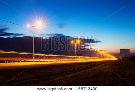 Sunset over highway with light trails, long exposure photo