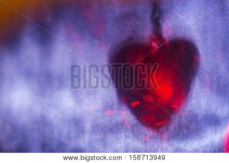 Red heart shape shadow on blue surface, abstract holiday background.