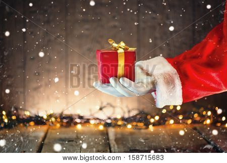 Santa Claus hand holding Christmas Gift box over wooden background. Proposing product. Advertisement gesture presenting point. Decorated Christmas tree with Winter Holiday Gifts.