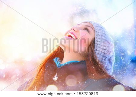 Winter young woman portrait. Beauty Joyful Model Girl raising hands, spinning and laughing, having fun in winter park. Beautiful young woman laughing outdoors. Enjoying nature, wintertime