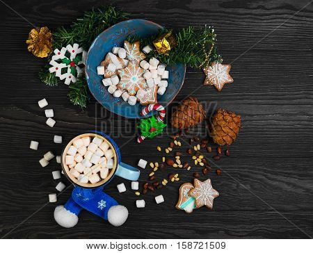 Christmas homemade gingerbread cookies hot drink chocolate marshmallow. Christmas snowflakes. Christmas drink hot cocoa chocolate in blue plate scarf. Ingredients for hot chocolate marshmallow nuts. Top view