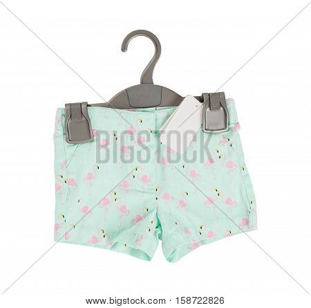 Green shorts with flamingo pattern on black plastic hanger with white blank label. Isolated on a white background.