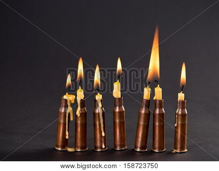 Burning candles and empty rifle cartridges. As a symbol of war and victims. Located on black cardboard as a background.