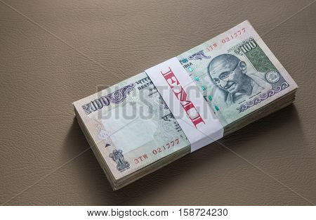 Bundle of hundred rupee notes wrapped with a band. Word 'EMI' written on the seal.