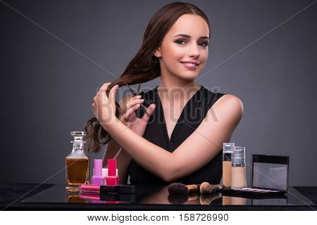 Beautiful woman applying make-up in fashion concept