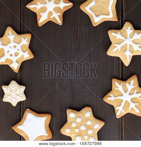 flat layout of the cookie in the shape of stars and snowflakes on a dark wooden background / frame appetizing winter snowstorm