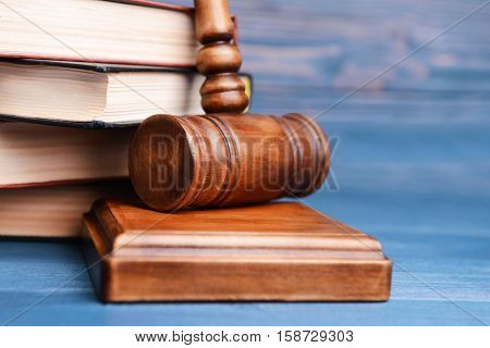 Judge's gavel and books on wooden wall background
