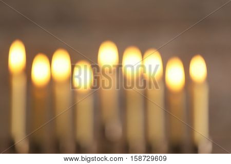 Blurred view of menorah with candles for Hanukkah on wooden background, close up
