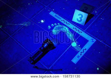 Hidden evidence under UV light on place of crime