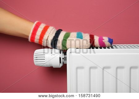Female hand in warm mitten on heating battery on pink background