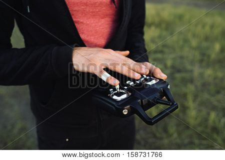 Man touching remote controller close-up, free space. Unrecognizable blind studying transmitter before piloting vehicle. Touch, modern technologies, life, leisure concept