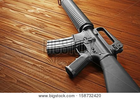 Close up view of assault rifle on wooden background