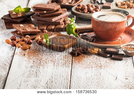 Assortment of different chocolate types and coffee on a white wooden background.