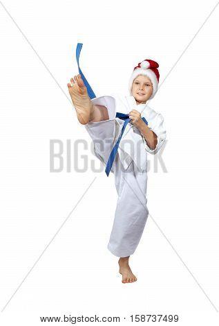 A boy with a blue belt and a cap of Santa Claus hits a kick leg