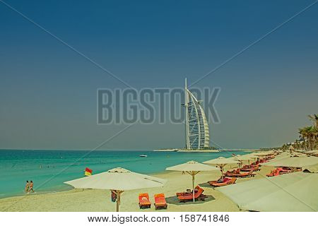 DUBAI, UAE - OCTOBER 14, 2016: The iconic Burj al Arab hotel in Dubai with a beach and umbrellas in the foreground. Built on a man made island, The Burj al Arab is the only 7 star hotel in the world