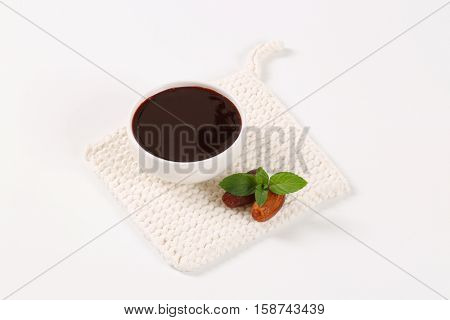 bowl of date syrup with dates on white table mat