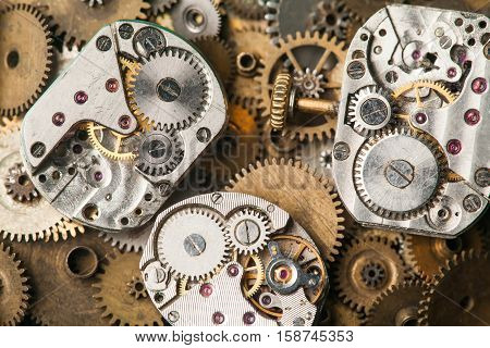 Vintage clocks mechanism close-up. Aged hand watches parts on bronze gears background. macro