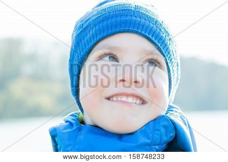 Cheerful little boy close-up headshot portrait with blue knitted hat