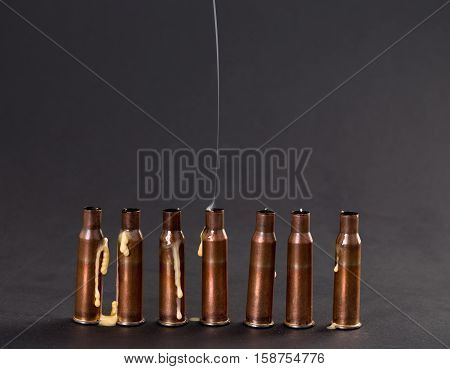 Empty rifle cartridges with smoke from the melted candles. As a symbol of war and victims. Located on black cardboard as a background.