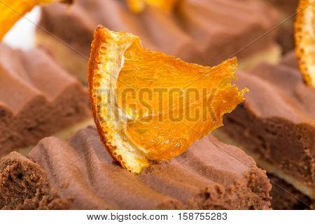 Delicious chocolate brownies with orange creme and sliced orange. Macro. Photo can be used as a whole background.