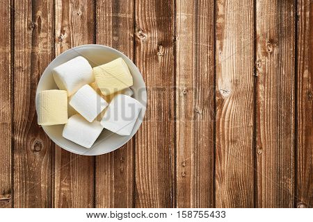 Marshmallow in bowl on wooden table top view