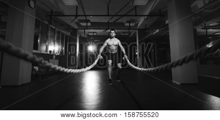 Fitness man working out with battle ropes at gym. Battle ropes fitness man at gym workout exercise fitted body. Fitness man training with battle rope in fitness club. Training with battle rope