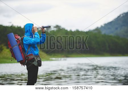 Traveler with big backpack looking through spyglass