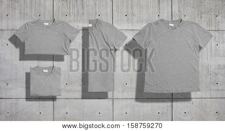 Unlabeled heather gray shortsleeve cotton t-shirt folded and lying flat as a set of four shots on concrete background for merchandise presentation