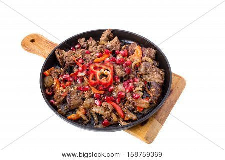 Stewed chicken livers with paprika and pomegranate seeds in cast iron pan. Isolated on a white background.