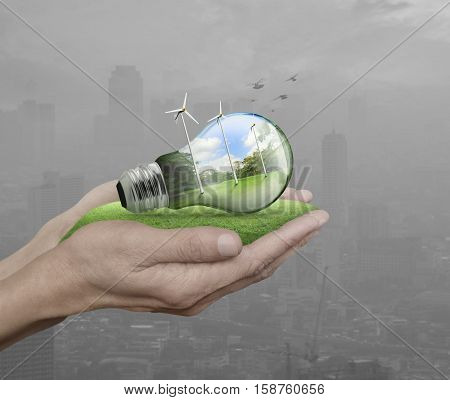Light bulb with wind turbines birds and forest inside in hands over pollution city Ecological concept