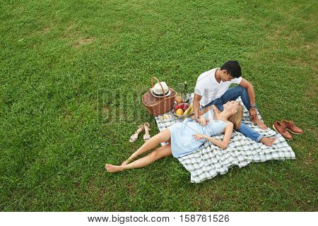 Young happy couple enjoying picnic in park