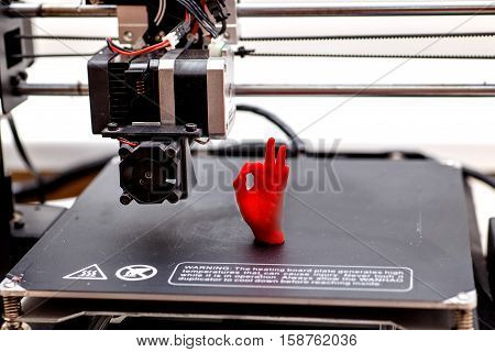 3d printing machine and printed item. palm plastic red