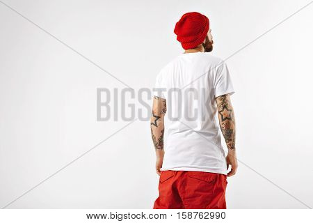 Snowboarder in red hat and pants and unlabeled white t-shirt shot from the back against white wall background