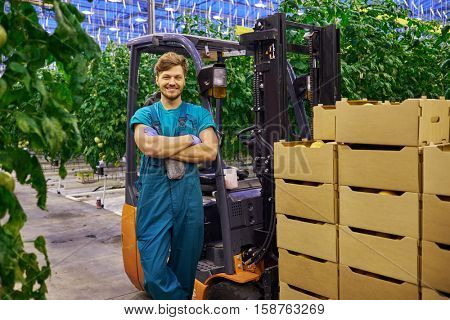 Young attractive man working on electric forklift in greenhouse.
