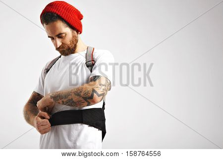 Young serious snowboarder in unlabeled white shortsleeve cotton t-shirt and red beanie putting on his back protector isolated on white
