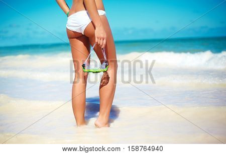 High fashion look. back of glamor sexy sunbathed model in white lingerie behind blue beach ocean water with water mask