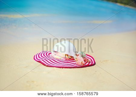 Colorful bright sunhat on the beach sand behind blue ocean summer water