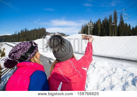 Two Girls Tourist Snowboard And Ski Resort Snow Winter Mountain Two Woman Taking Selfie Photo On Cell Smart Phone